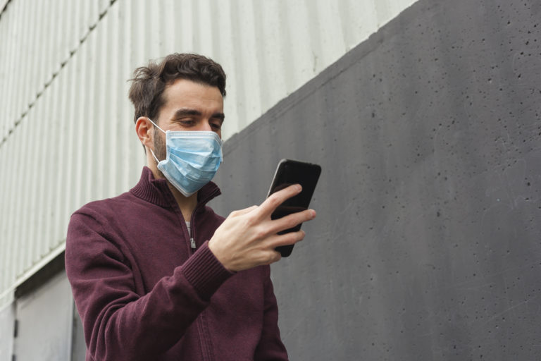 Bearded adult man using smartphone while wearing surgical mask