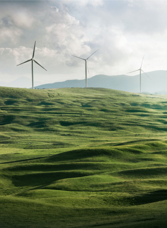 Three Windmills on green hills in front of a stormy sky