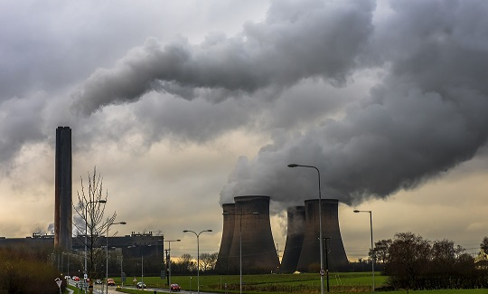 A UK power plant with cooling towers venting steam