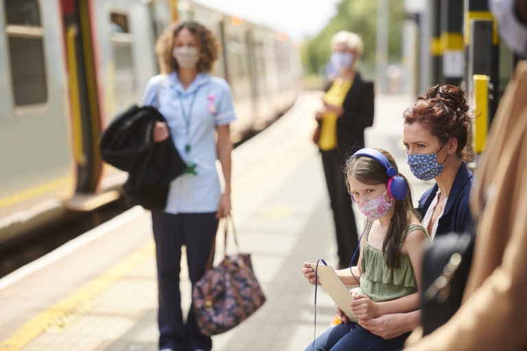 Image of girl and mother sitting on train platform in masks