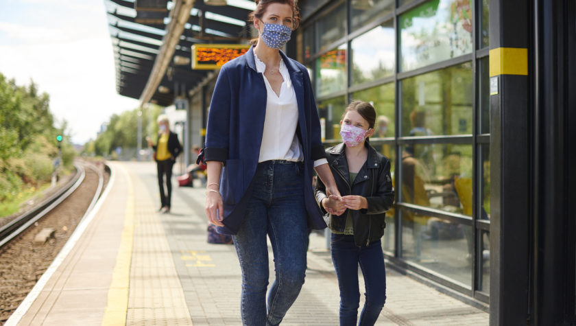 Mother and daughter wearing face masks while using a train station