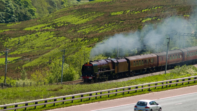 A Princess Coronation (Duchess) class express steam locomotive steaming fast up the west coast main line on the fringes of the English Lake District. A car travelling in the opposite direction is on the adjacent M6 motorway.