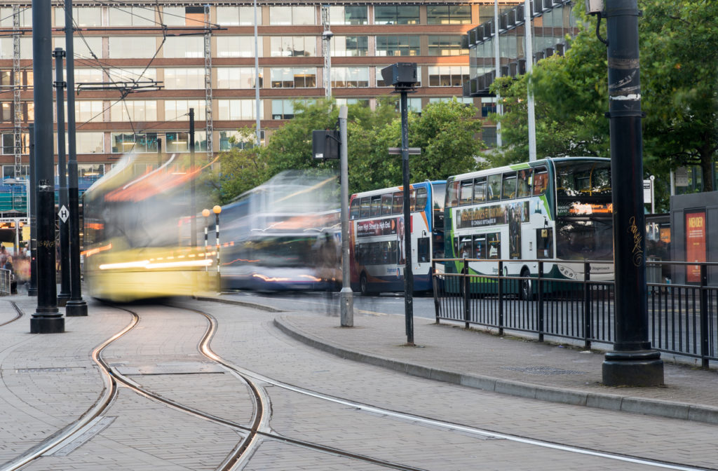 Piccadilly central bus and metro station with moving tram and buses in Piccadilly gardens at the city of Manchester in England
