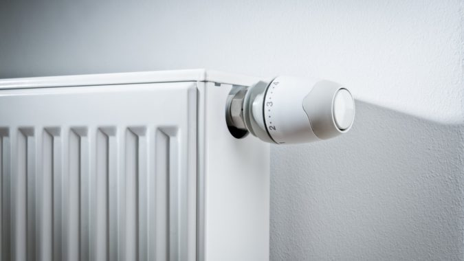 Modern white radiator with thermostat reduced to economy mode