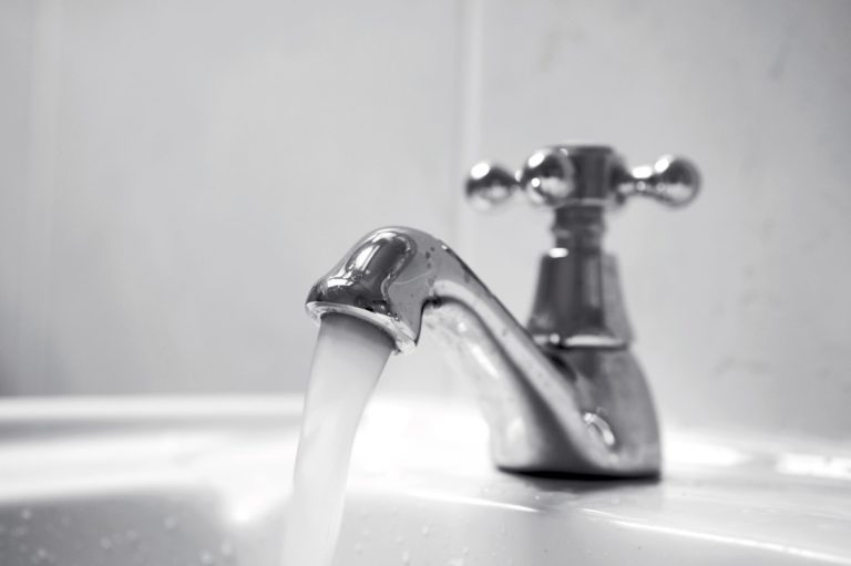 Close up of chrome tap, water running